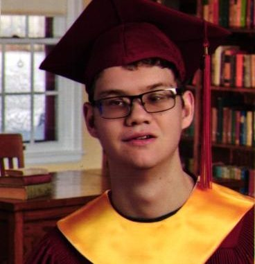 Bryce wearing a maroon cap and gown with the gold collar is standing in a library.
